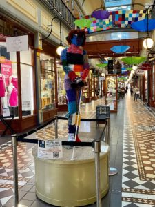 A mannequin stands on a pedestal in an arcade walkway. It is decorated in yarn and knitting and holds a cane.