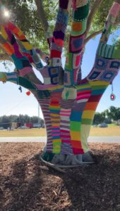 A large tree with lots of branches is covered in colourful yarn and knitting