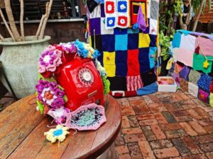 A red telephone sits on a wooden table. Crocheted flowers hang over it. Behind, two large knitted blankets cover objects.